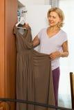 Rijpe vrouw die kleding thuis kiest Royalty-vrije Stock Foto's