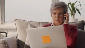Rijpe vrouw die laptop bekijken en op cellulair spreken stock footage