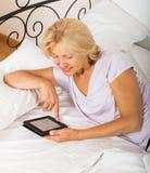 Rijpe vrouw die met ereader op bed leggen Stock Afbeeldingen