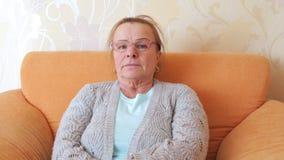 Rijpe vrouw die met glazen zorgvuldig de camera bekijken stock footage
