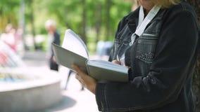 Rijpe vrouw die nota's in een agenda in een park maken stock video