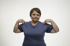 Rijpe vrouw die oefening met een grijze achtergrond maken Stock Afbeeldingen