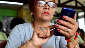 Rijpe vrouw die omhoog het slimme doorbladeren van telefooninternet scrollen stock video