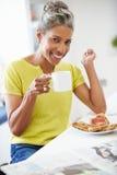 Rijpe Vrouw die Ontbijt eet en Krant leest royalty-vrije stock foto's