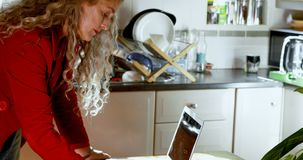 Rijpe vrouw die op blocnote in keuken 4k schrijven