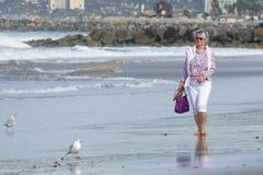 Rijpe vrouw die op strand lopen stock foto