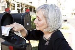 Rijpe vrouw die post terugwint Stock Foto's