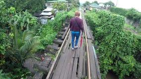 Rijpe vrouw die rottende spoorwegbrug kruisen stock video