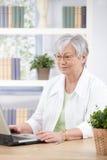 Rijpe vrouw die thuis aan laptop werkt Stock Foto