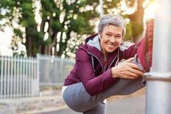 Rijpe vrouw die vóór jogging opwarmen stock afbeeldingen