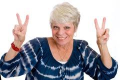 Rijpe vrouw die vredesteken geeft Stock Afbeelding