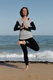Rijpe vrouw die yoga op het strand doen Royalty-vrije Stock Foto