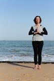 Rijpe vrouw die yoga op het strand doen Stock Afbeeldingen