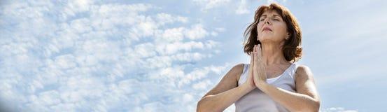 Rijpe vrouw die in yogapositie bidden met blauwe hemel, banner stock afbeelding