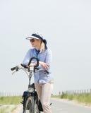 Rijpe vrouw die zich met fiets op straat bevinden Royalty-vrije Stock Afbeeldingen