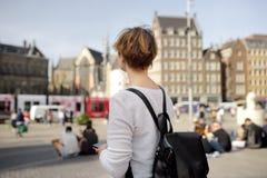 Rijpe vrouw die zich op een Zonnige de herfstdag bevinden in het Centrale damvierkant in de oude stad van Amsterdam met nadruk op royalty-vrije stock afbeelding