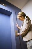 Rijpe vrouw door de lift Stock Foto's