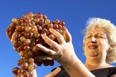 Rijpe vrouw en druiven Royalty-vrije Stock Foto's