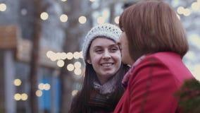 Rijpe vrouw en haar gegroeide dochterzitting op een bank in het stad park en het bespreken Warme Verhouding Moeder ` s stock videobeelden