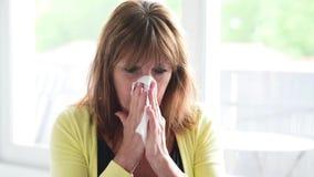 Rijpe vrouw met allergie die en haar neus blazen niezen stock video