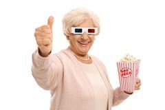 Rijpe vrouw met 3D glazen en popcorn die een duim op gestu maken Royalty-vrije Stock Afbeeldingen