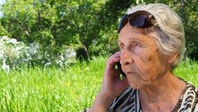 Rijpe vrouw met een telefoon Een teruggetrokken vrouw spreekt op haar mobiele telefoon in het park Oude vrouw in zonnebril met stock videobeelden