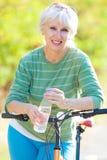 Rijpe vrouw met fiets Stock Afbeelding