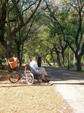 Rijpe vrouw met fiets, die op een bank in een park lezen Stock Foto's