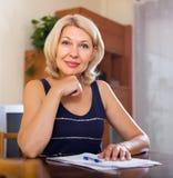 Rijpe vrouw met financiële documenten royalty-vrije stock afbeelding