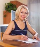 Rijpe vrouw met financiële documenten royalty-vrije stock fotografie