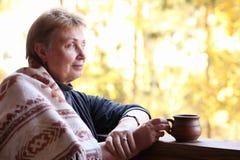 Rijpe vrouw met kop thee en wollen plaid op terrasloo stock foto's
