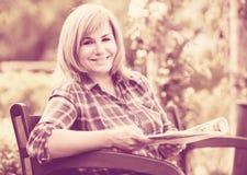 Rijpe vrouw met tijdschrift in tuin Stock Fotografie