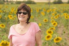 Rijpe vrouw met zonnebril op een gebied van zonnebloemen royalty-vrije stock fotografie
