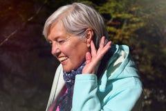 Rijpe vrouw in middenleeftijd met aardig grijs haar openlucht in aardportret stock foto's