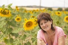 Rijpe vrouw op een gebied van zonnebloemen royalty-vrije stock foto's