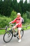 Rijpe vrouw op fiets in bos royalty-vrije stock fotografie