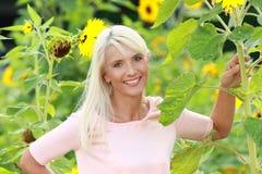 Rijpe vrouw op het gebied van de zonbloem Stock Foto's
