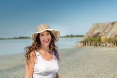Rijpe vrouw op zon gespleten strand stock foto
