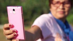 Rijpe vrouw zelfportretten zelf met het gebruik van mobiele smartphone