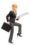 Rijpe vrouwelijke architect met de blauwdrukken van de helmholding Stock Afbeelding