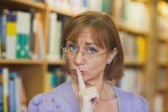 Rijpe vrouwelijke bibliothecaris die een teken geven om te zijn stille status in bibliotheek royalty-vrije stock afbeelding