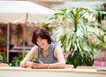 Rijpe vrouwelijke het gebruiken smartphone Royalty-vrije Stock Foto's