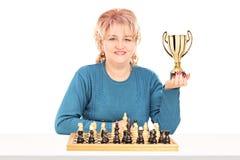 Rijpe vrouwelijke schaakspeler die een trofee houden Royalty-vrije Stock Foto's