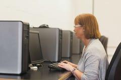 Rijpe vrouwelijke student in computerklasse Stock Afbeelding