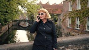 Rijpe Vrouwenonderneemster Talking On Phone in de Straat bij het Rivierkanaal stock videobeelden