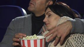 Rijpe vrouwenslaap op de schouder van haar echtgenoot bij de bioskoop royalty-vrije stock afbeelding