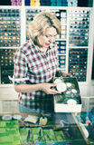 Rijpe vrouwenverkoper die zich bij teller met kleine spelden bevinden Royalty-vrije Stock Afbeelding