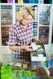 Rijpe vrouwenverkoper die zich bij teller met kleine spelden bevinden Stock Foto's