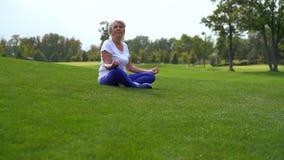 Rijpe vrouwenzitting op gras in een park stock videobeelden
