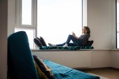 Rijpe vrouwenzitting op het bed van de vensterrichel stock foto's